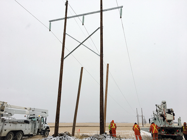 Crews installing power pole